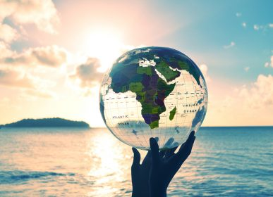 a transparent globe showing the map of Africa is held in silhouetted hands and raised against a bright sunset and beach horizon. A perfect concept about global environmental issues such as global warming and eco friendly and renewable energy themes